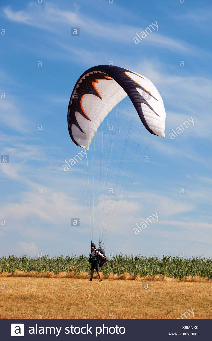 Germany, Moselle, Person parachuting landing on landscape Stock Photo