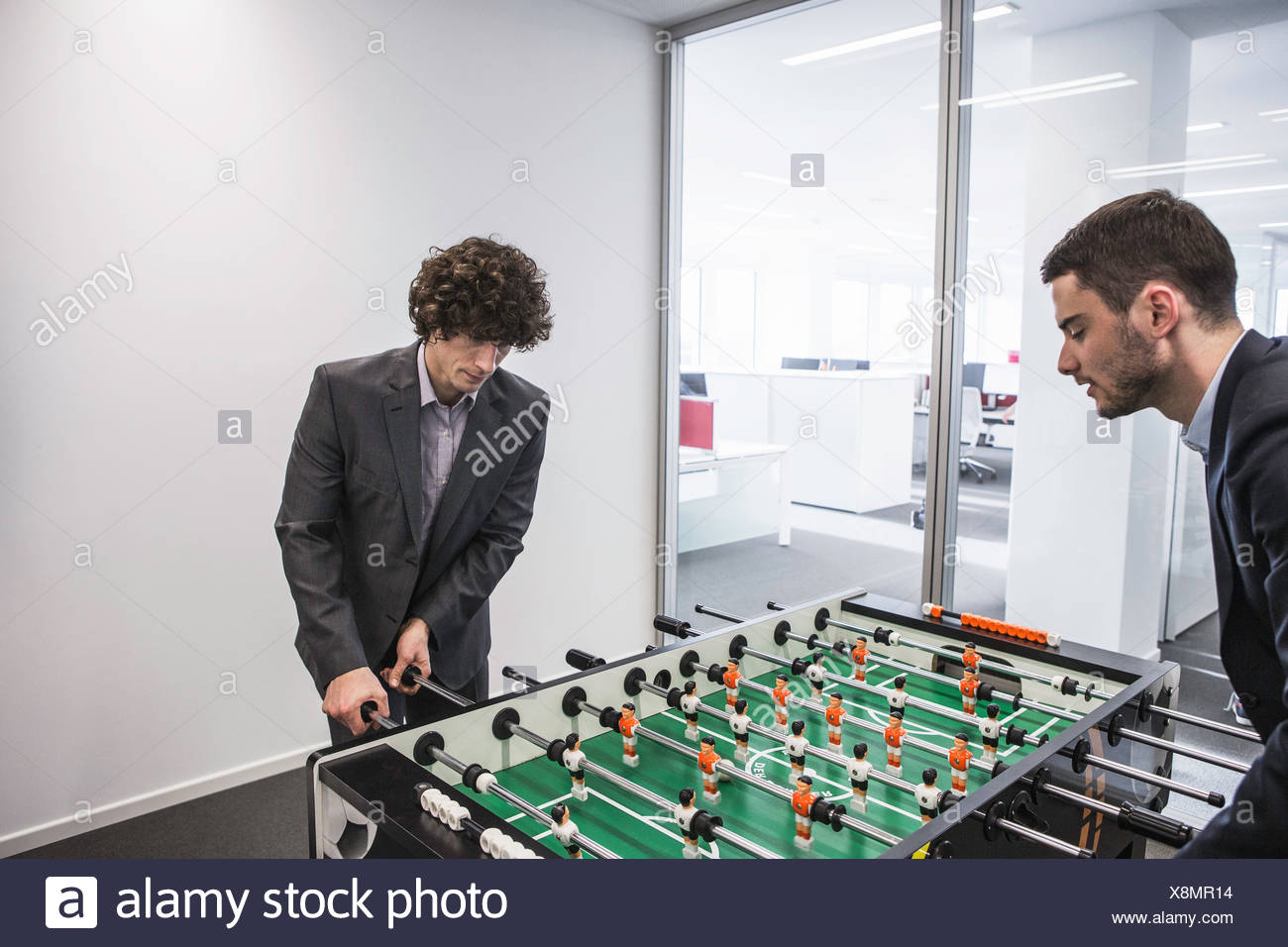 Businessmen playing table football Stock Photo