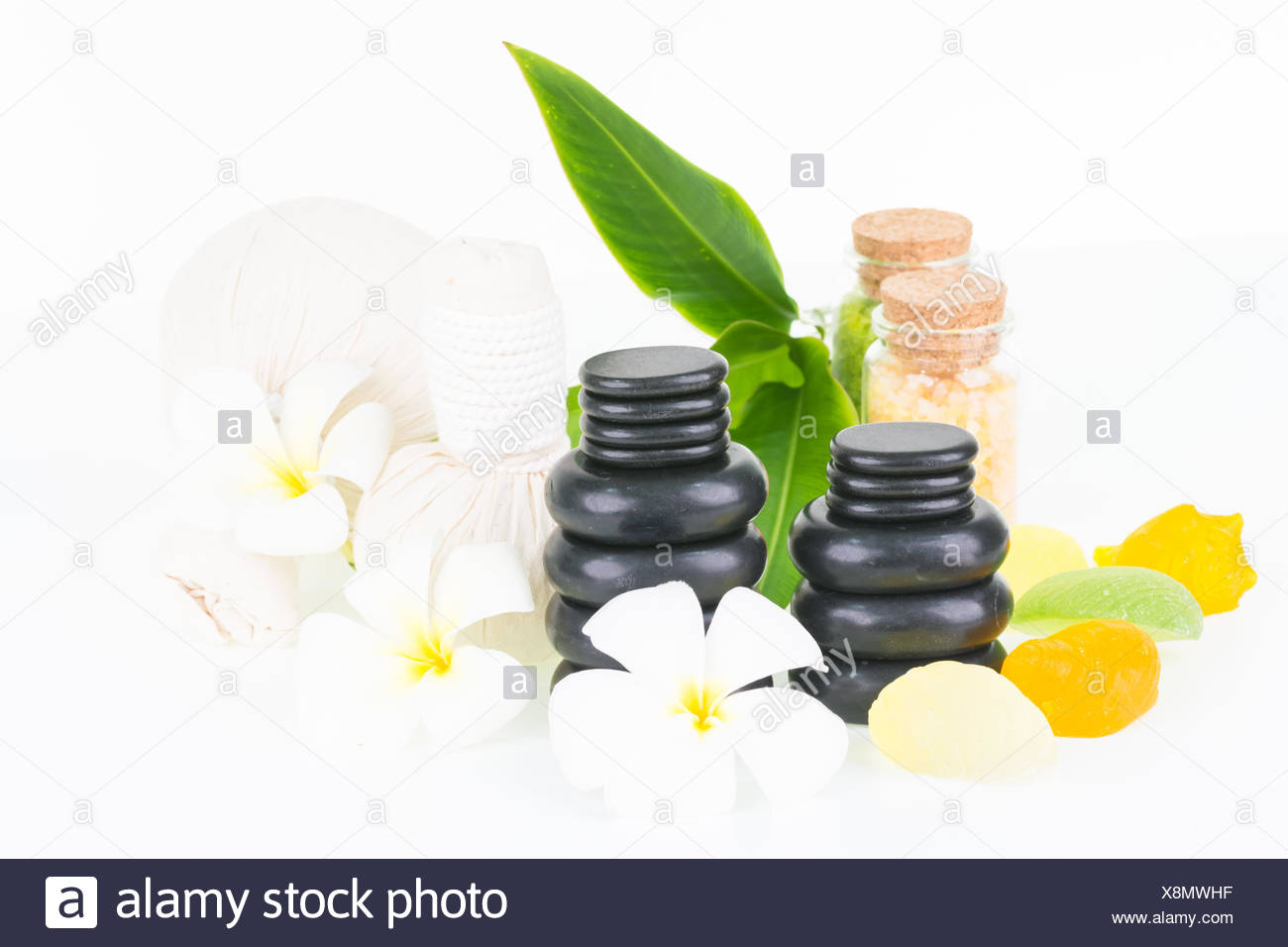 Tropical spa getaway with herbal compress balls, seashell shaped soaps, hot stones and bath salt - Stock Image
