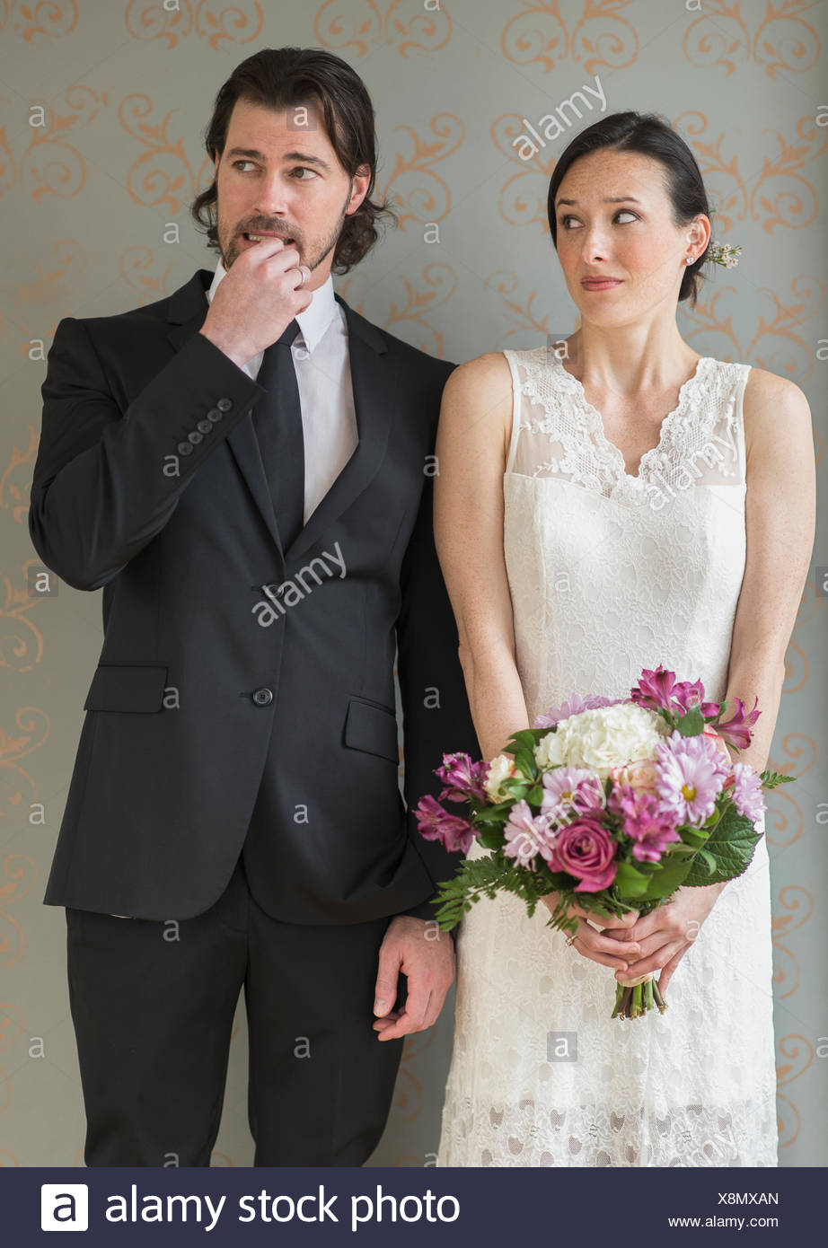 Anxious bride and groom posing with bunch of flowers - Stock Image