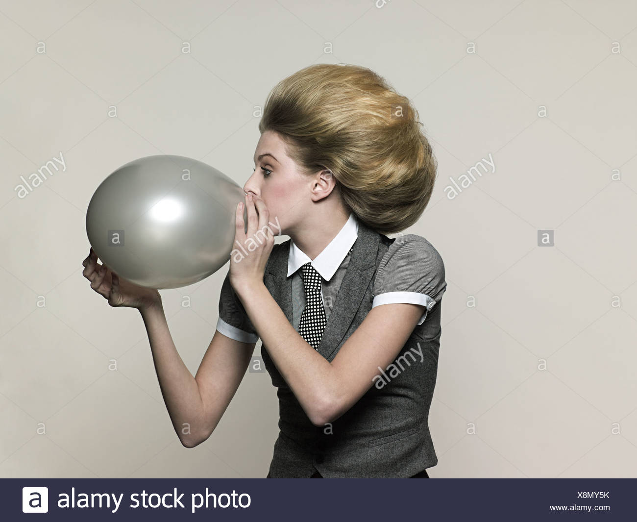 Businesswoman blowing balloon - Stock Image
