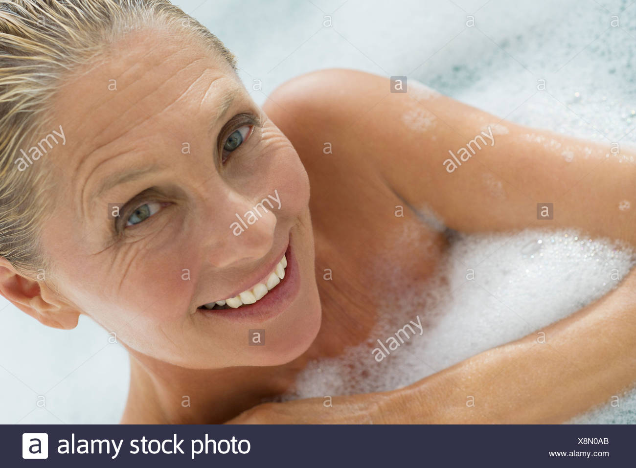 Mature woman enjoying bubble bath, tilt - Stock Image