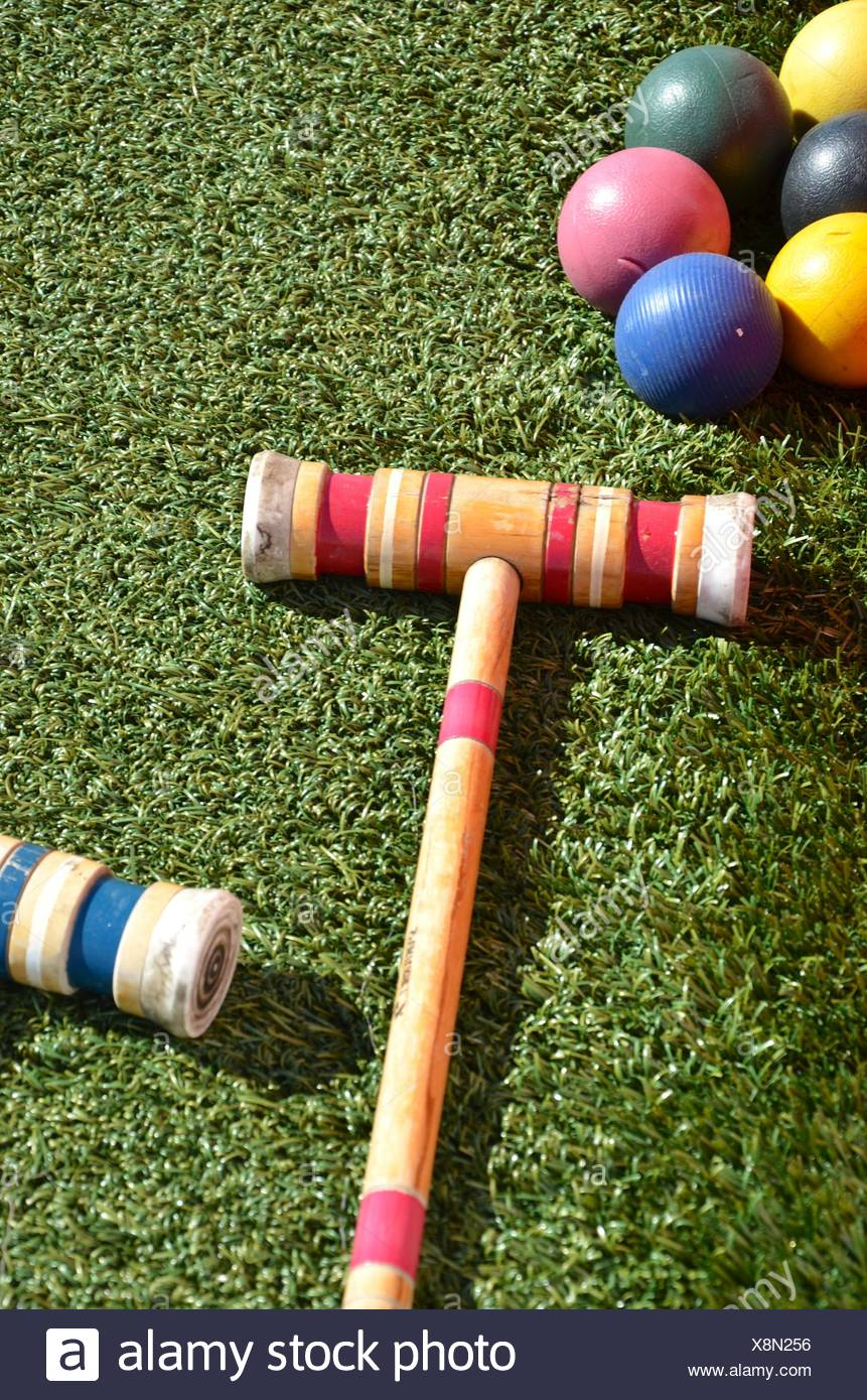 Croquet mallets and varicolored balls on artificial turf - Stock Image