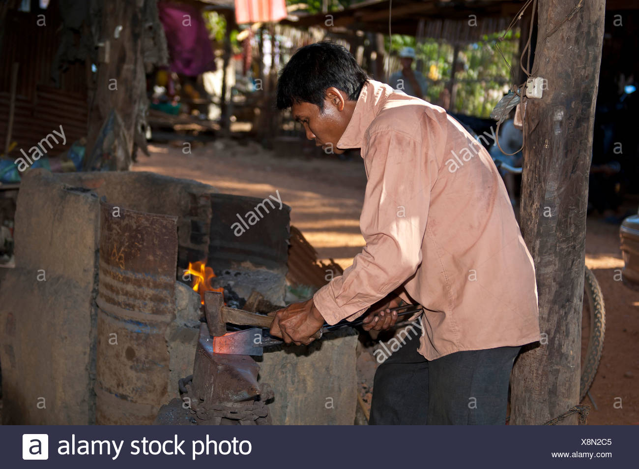 Blacksmith forging red-hot iron in a forge, Battambang, Cambodia - Stock Image