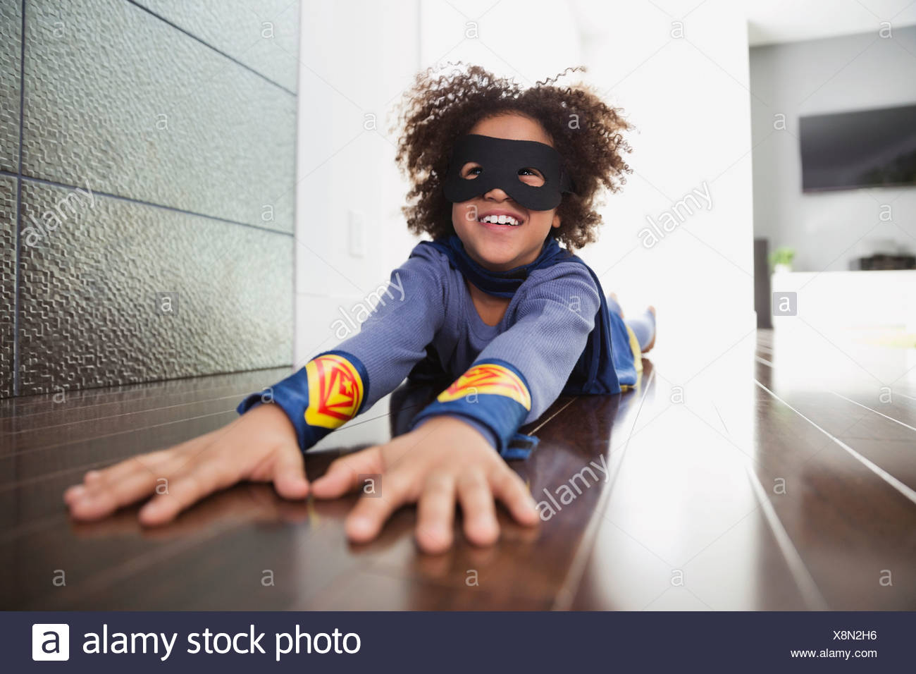 Boy pretending to be superhero at home - Stock Image