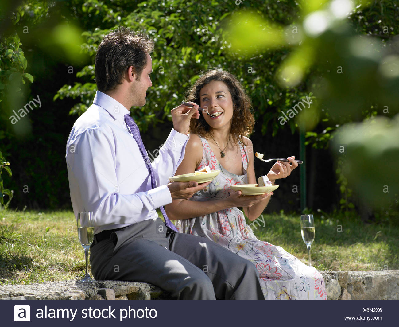 Wedding guests feeding each other cake - Stock Image