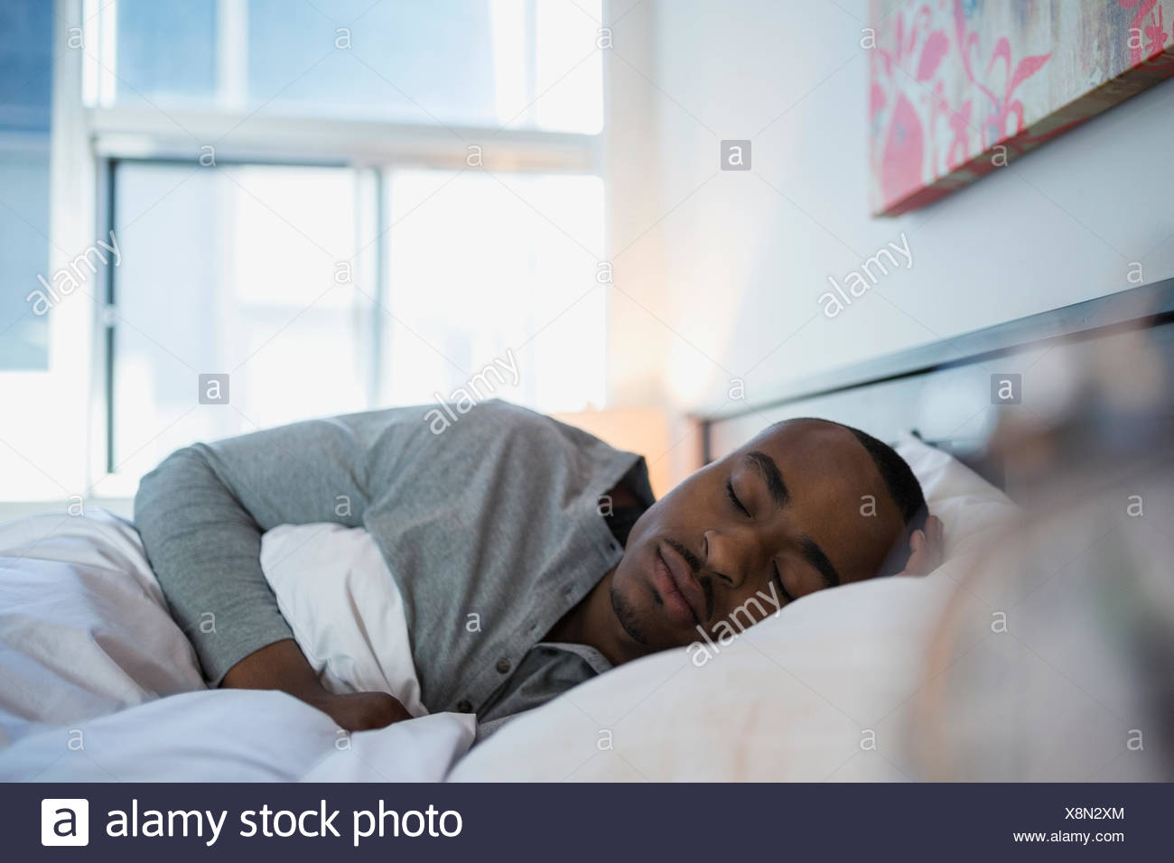 Serene man sleeping in bed in the morning - Stock Image