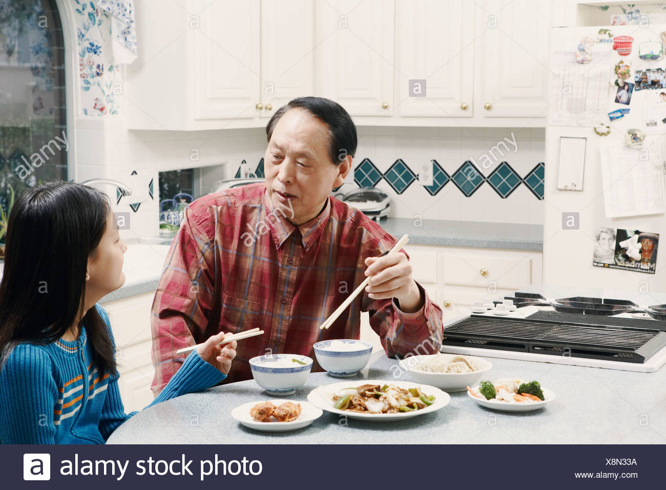 Grandfather and his granddaughter sitting at a table Stock Photo