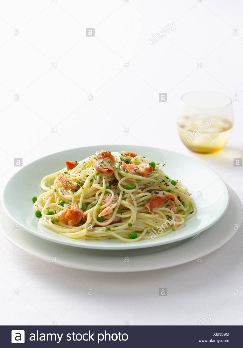 Plate of fish and pea pasta - Stock Image