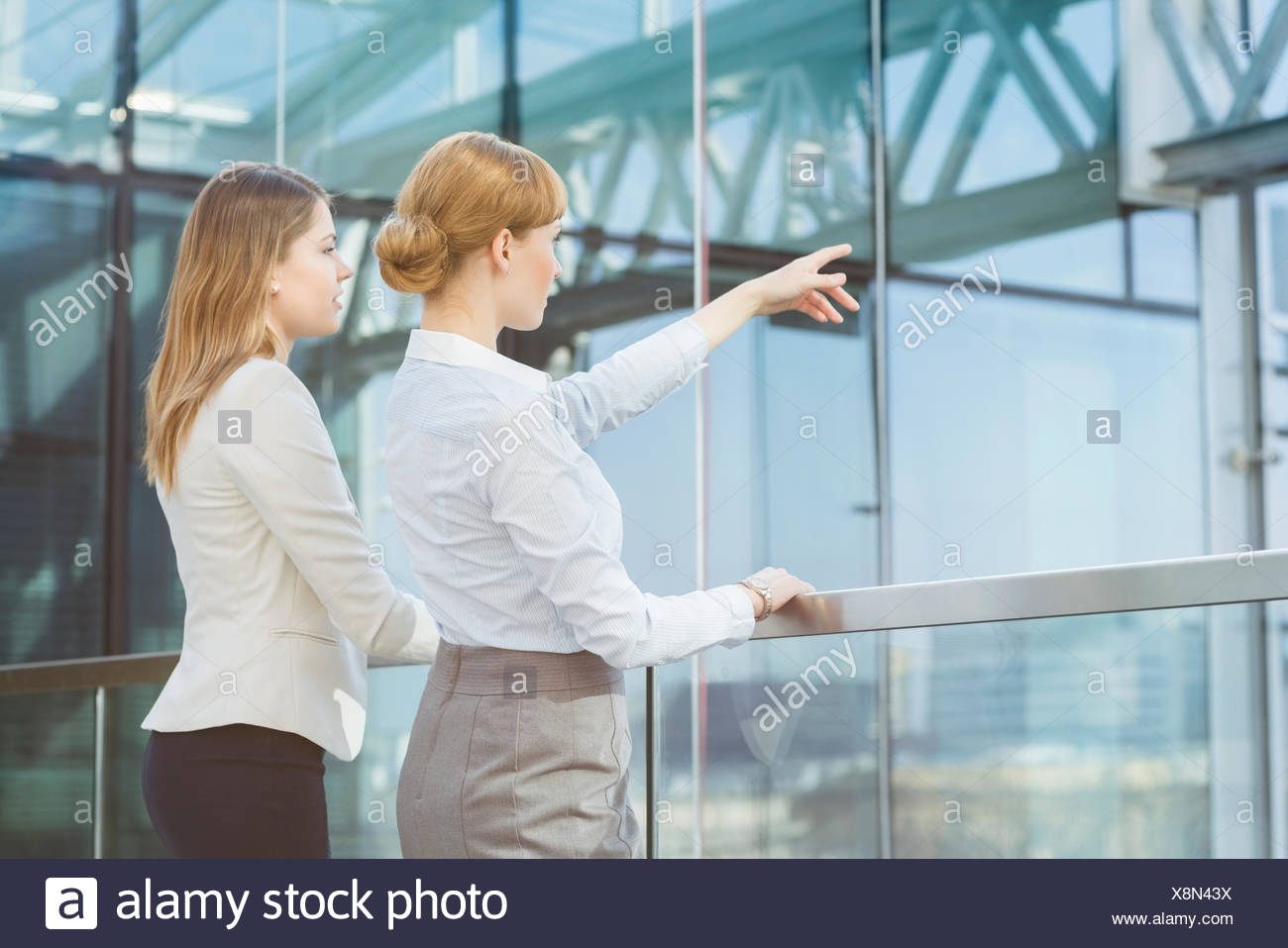 Businesswoman showing something to female colleague from glass wall in office - Stock Image