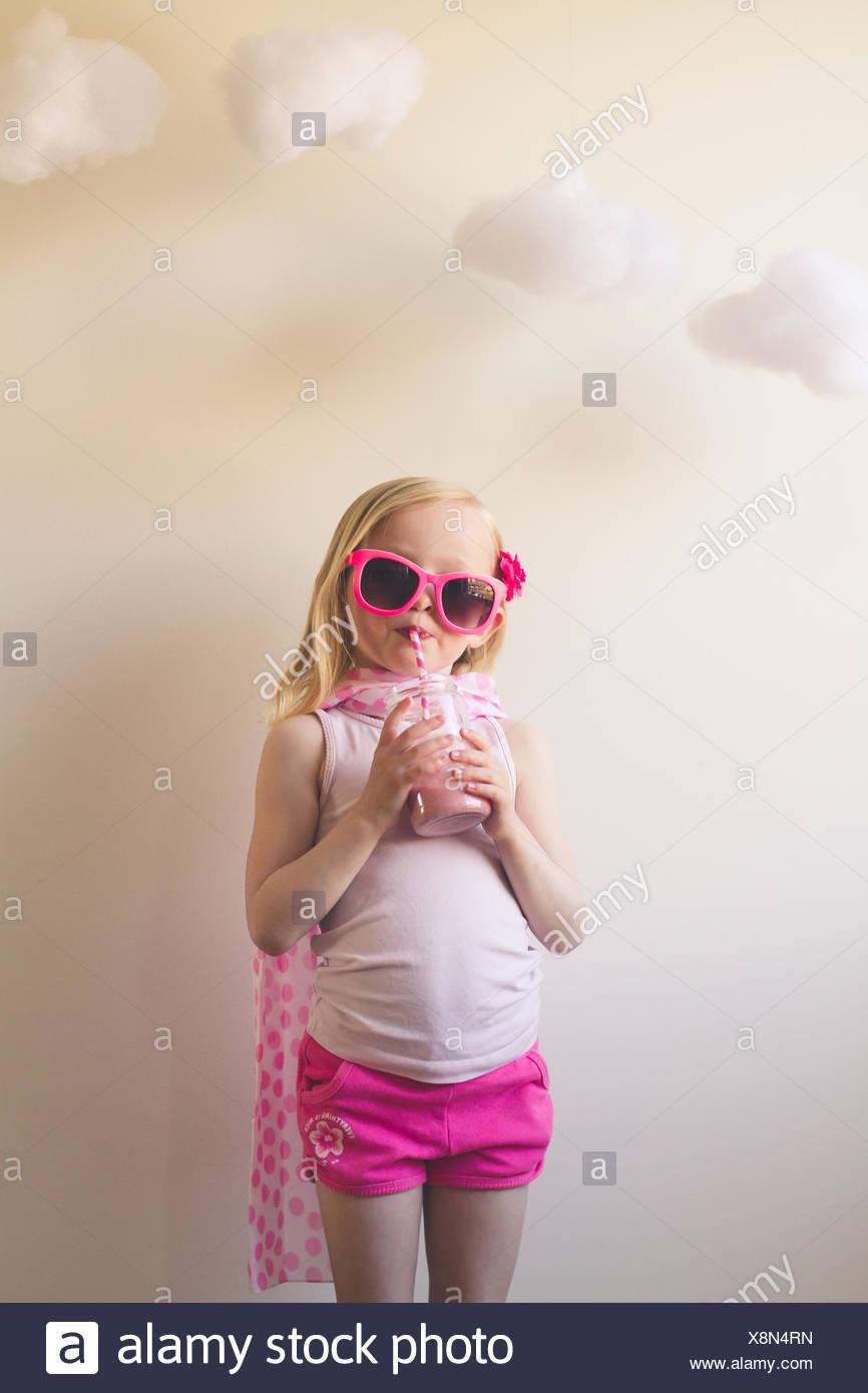 Girl in pink drinking a pink milkshake - Stock Image