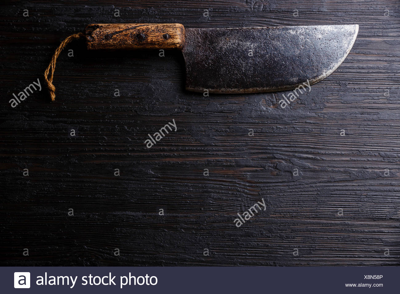 Vintage Butcher meat cleaver knife on dark burned wooden background copy space - Stock Image