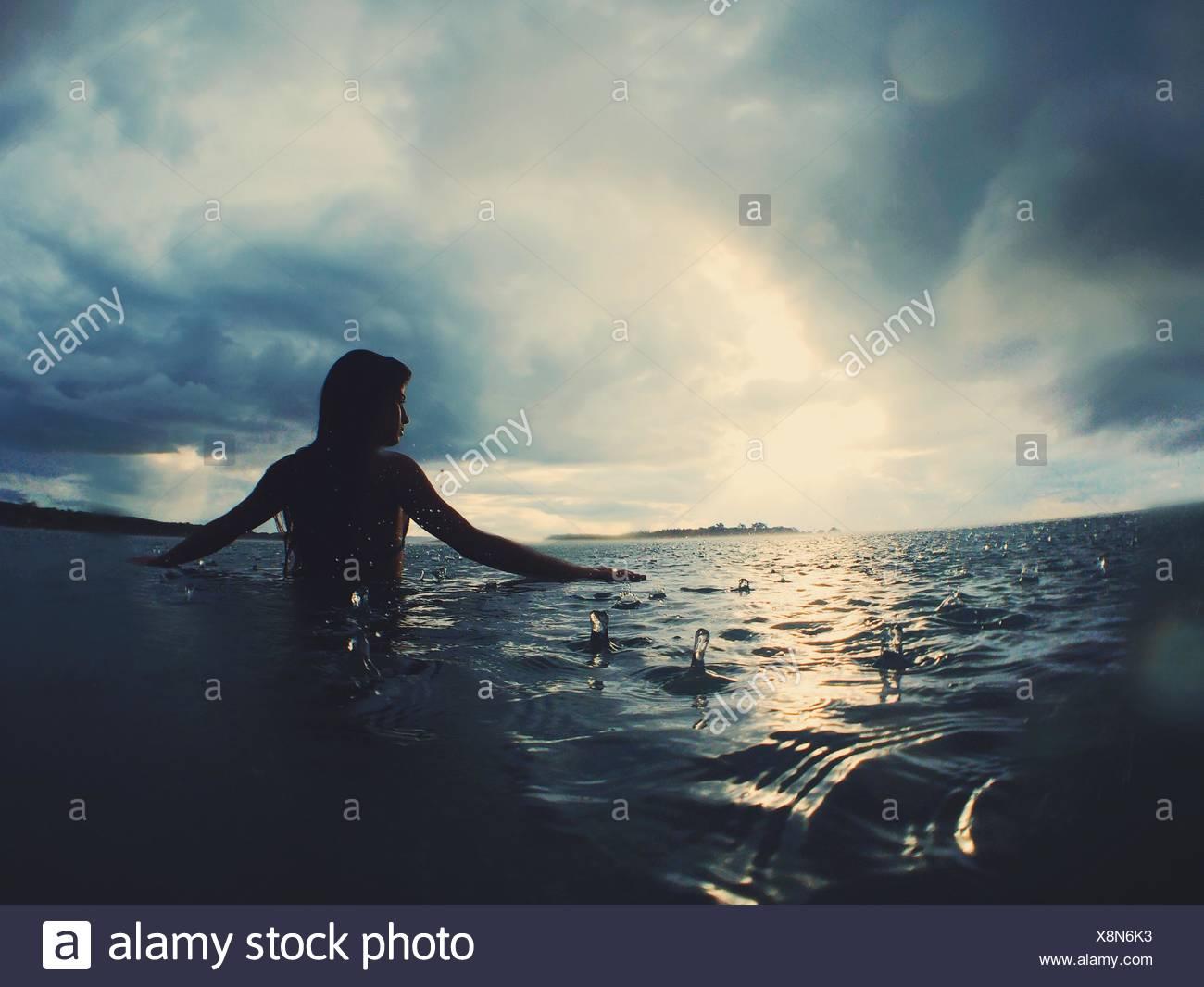 Woman in sea in rain - Stock Image