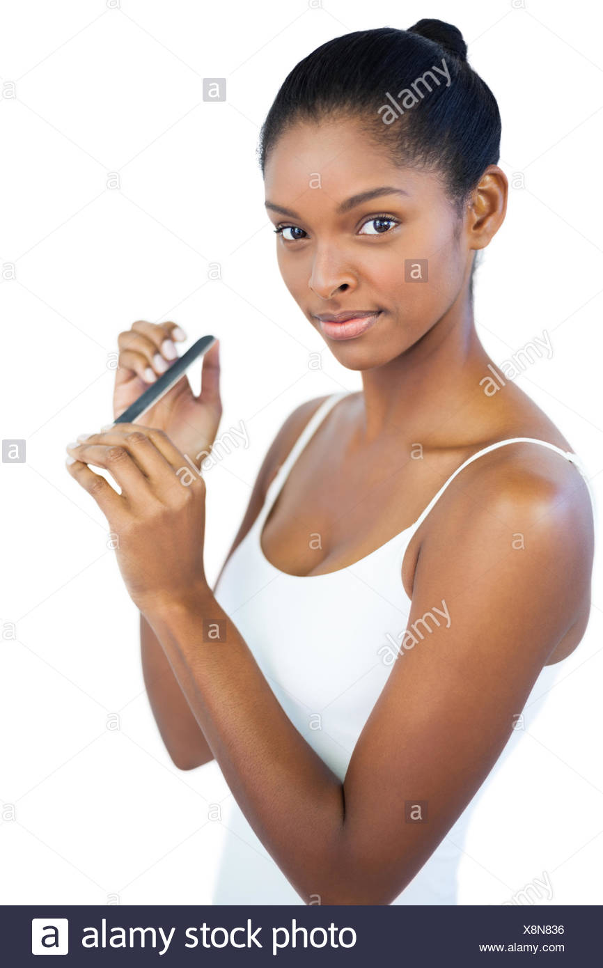 Young woman using nail file on white background Stock Photo