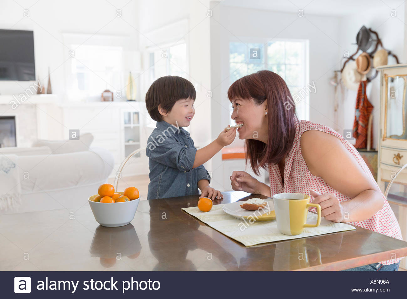 Playful son feeding mother at dining table - Stock Image