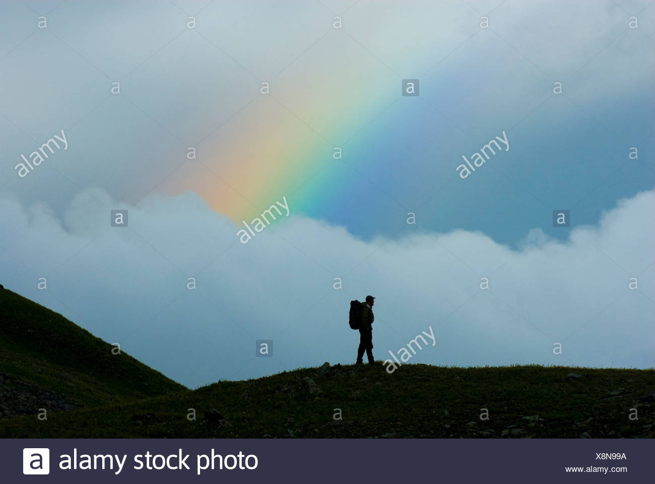 Man standing on ridge in front of rainbow, San Juan National Forest, Colorado (silhouette). - Stock Image