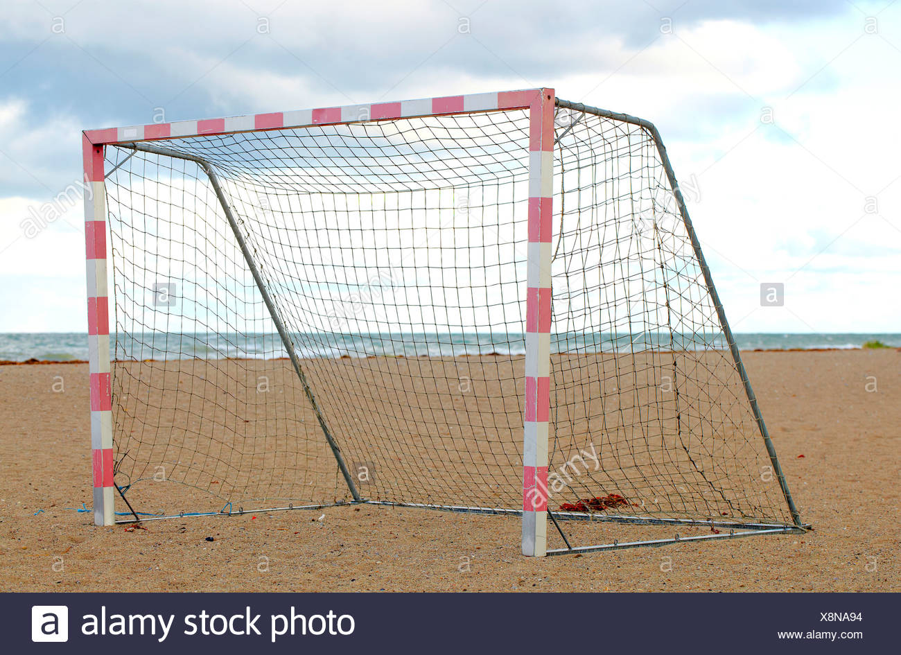 Lone soccer net on the beach against cloudy sky - Stock Image