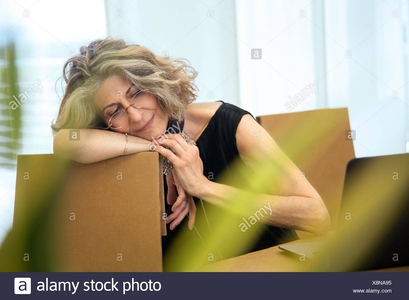 Senior businesswoman relaxing on office chair - Stock Image