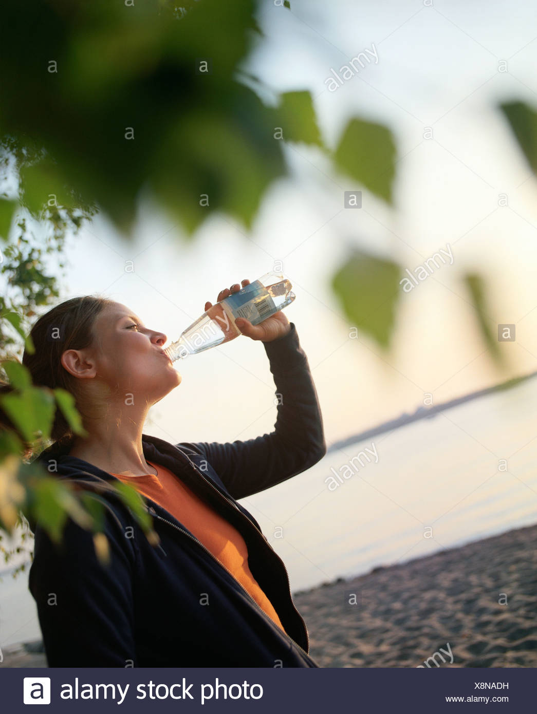 Side profile of a young woman drinking water from a bottle on the beach - Stock Image