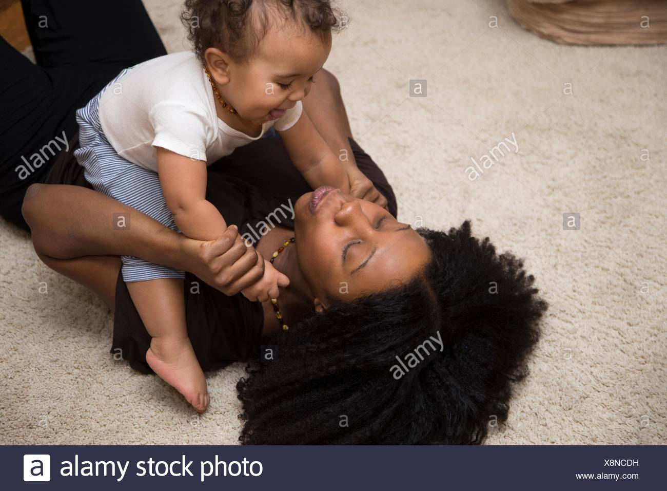 Mid adult woman playing with toddler daughter on rug - Stock Image