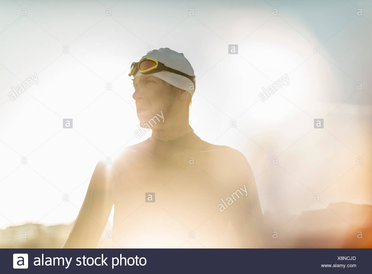 A swimmer in a wet suit, swimming hat and goggles. - Stock Image