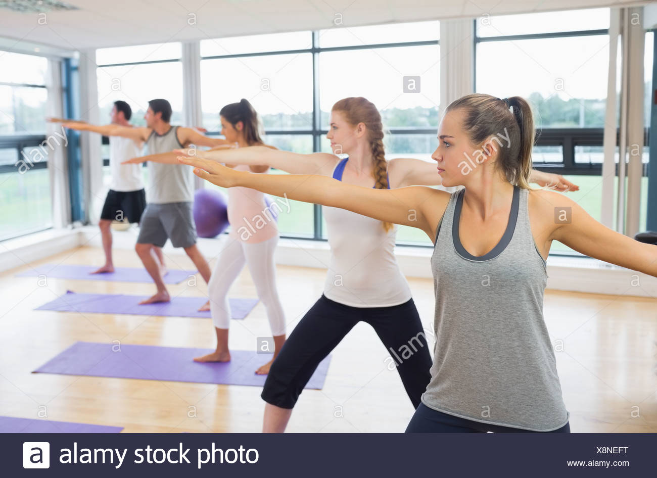 Sporty people stretching hands at yoga class - Stock Image