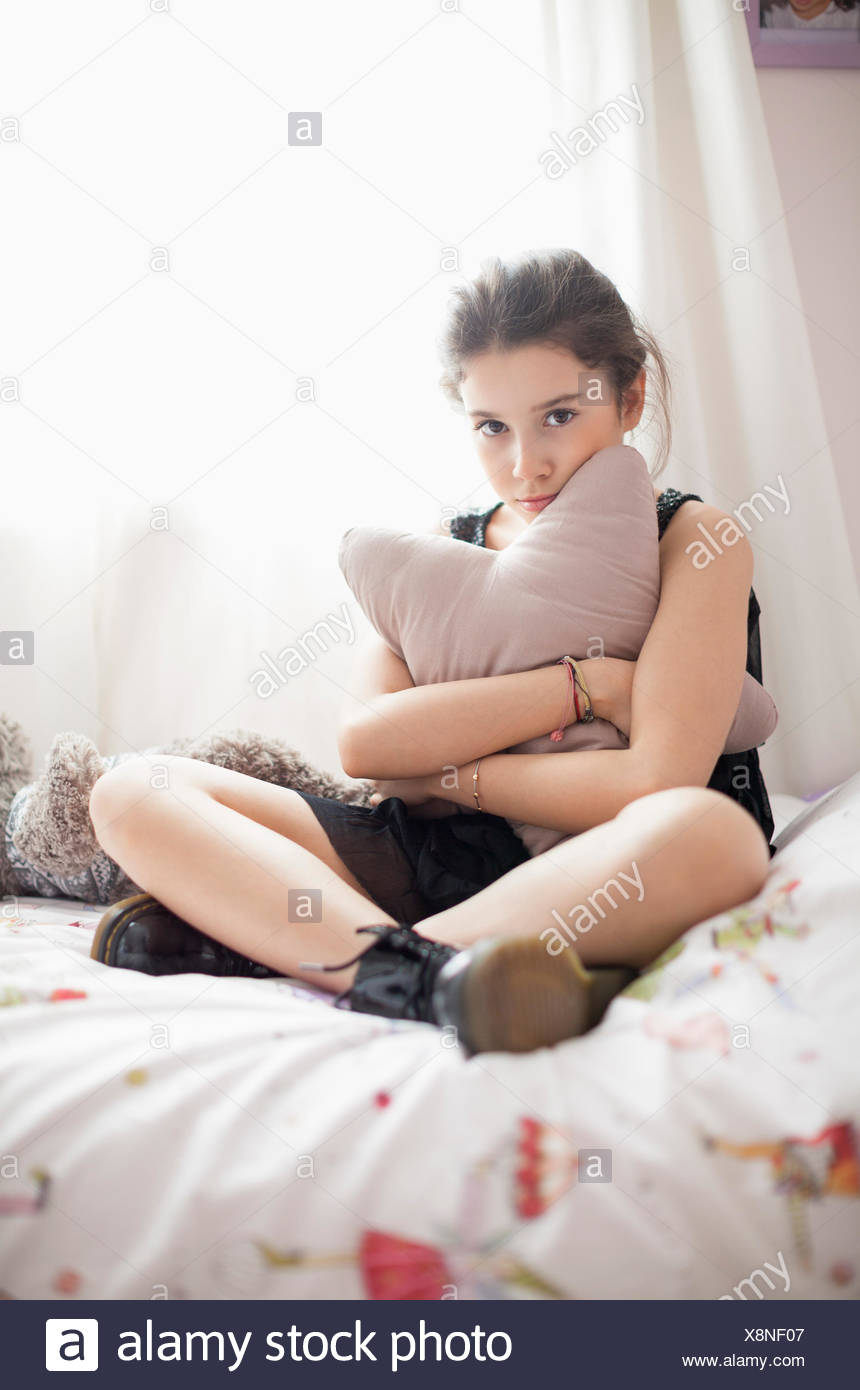 Girl looking serious on the bed - Stock Image