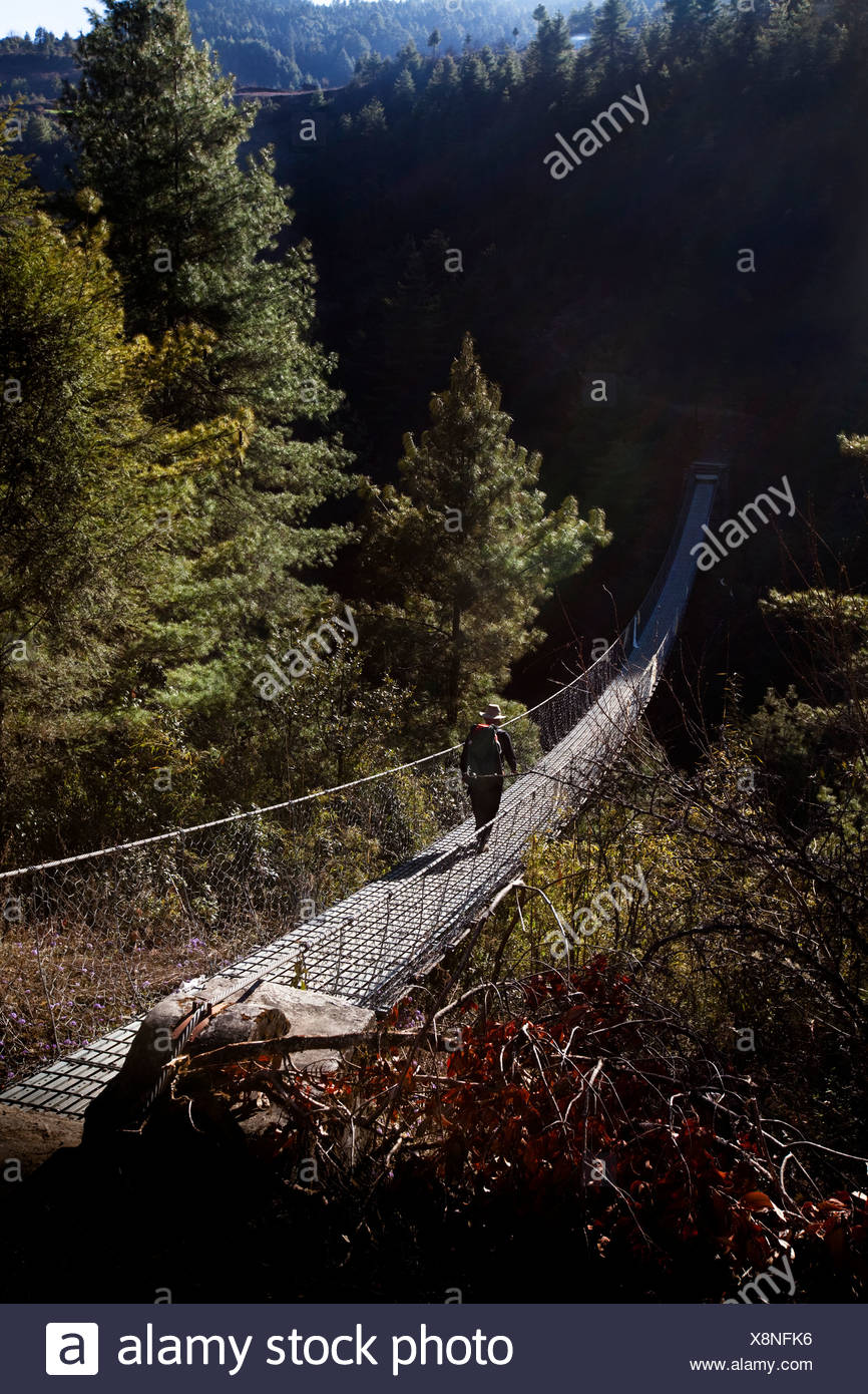 A lone trekker crossing a suspension footbridge in Nepal. - Stock Image