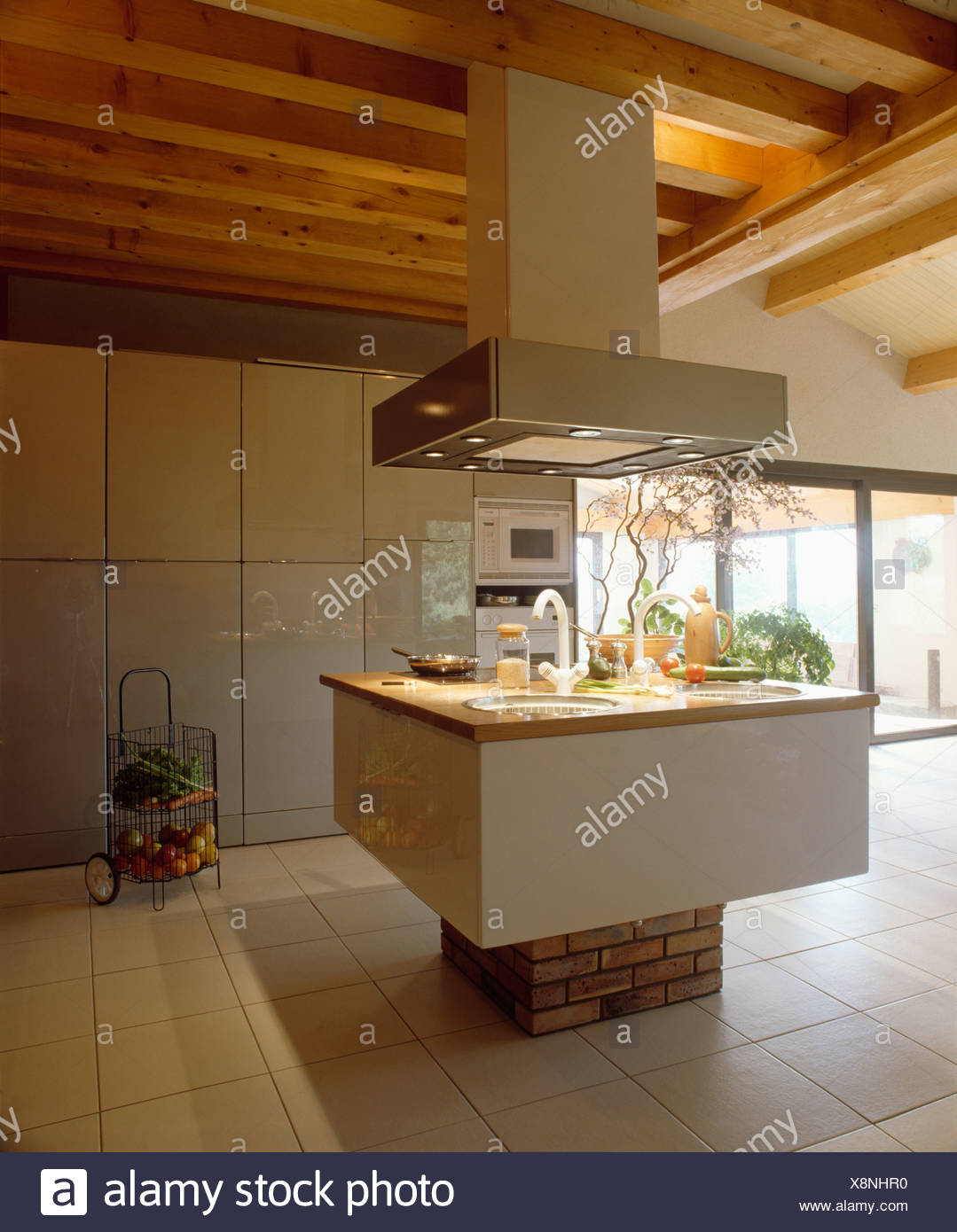 Large Extractor Fan Above Sink In Island Unit In Modern White Kitchen With Wooden Ceiling Beams Stock Photo Alamy