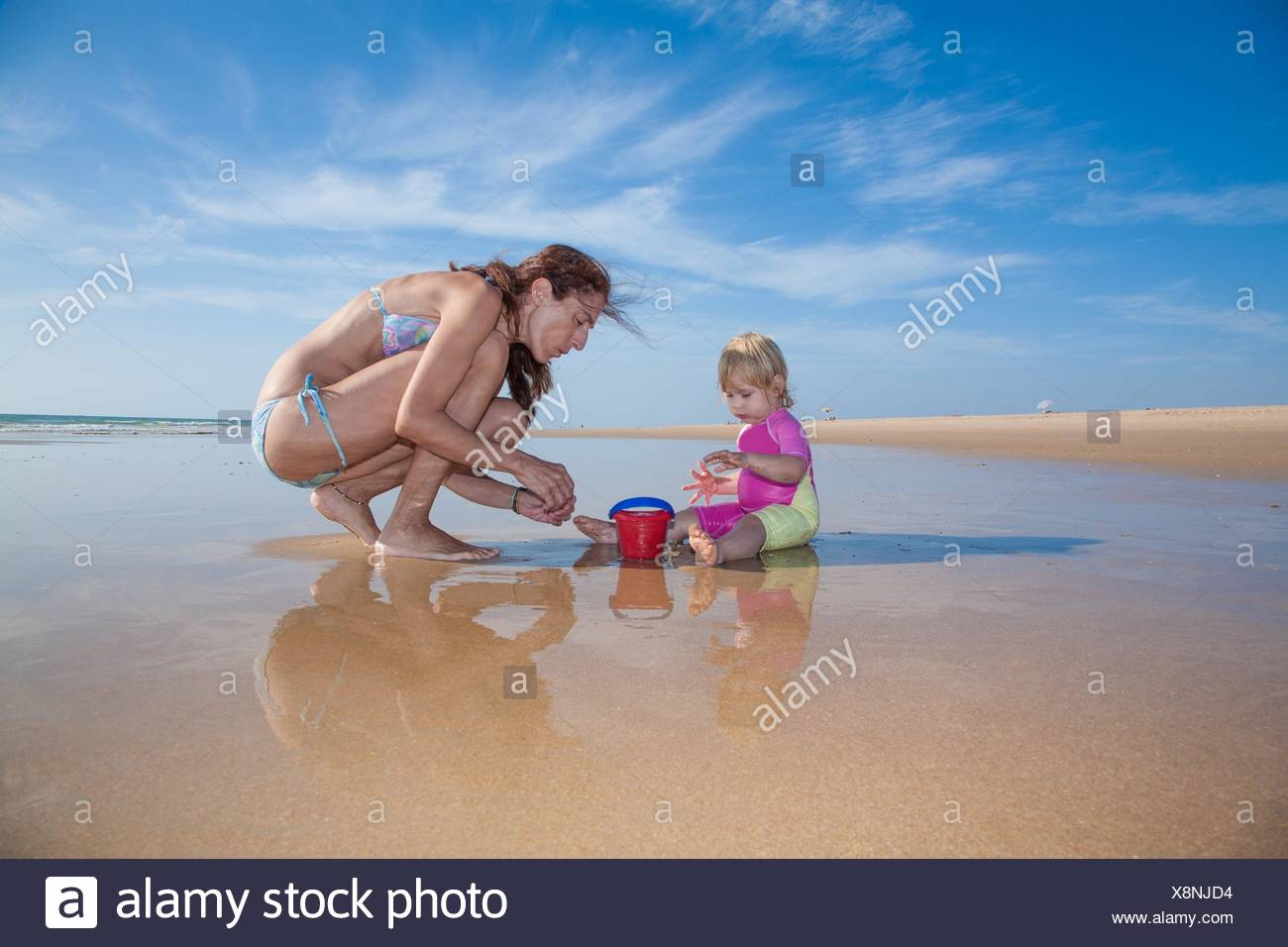 summer family of two years blonde baby pink and yellow swimsuit sitting on water with brunette woman mother in bikini with red plastic bucket at sea - Stock Image