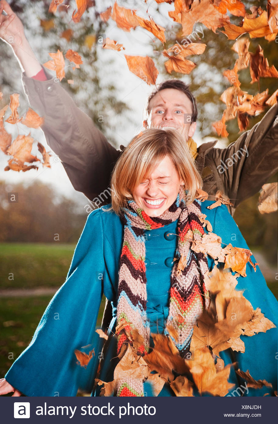 Couple playing with autumn leaves - Stock Image