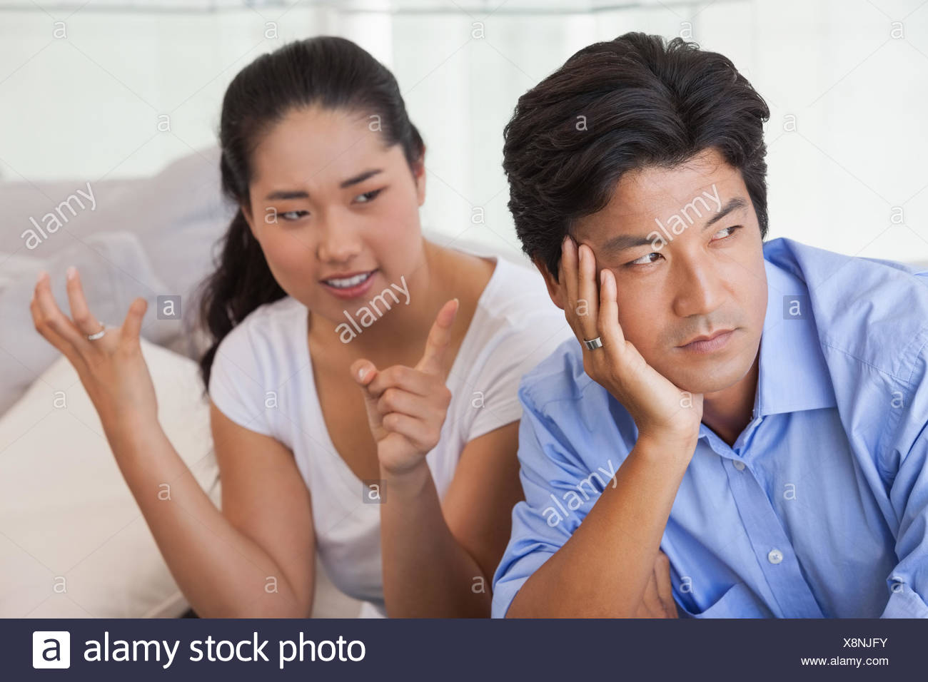 Couple sitting on the couch having a fight - Stock Image