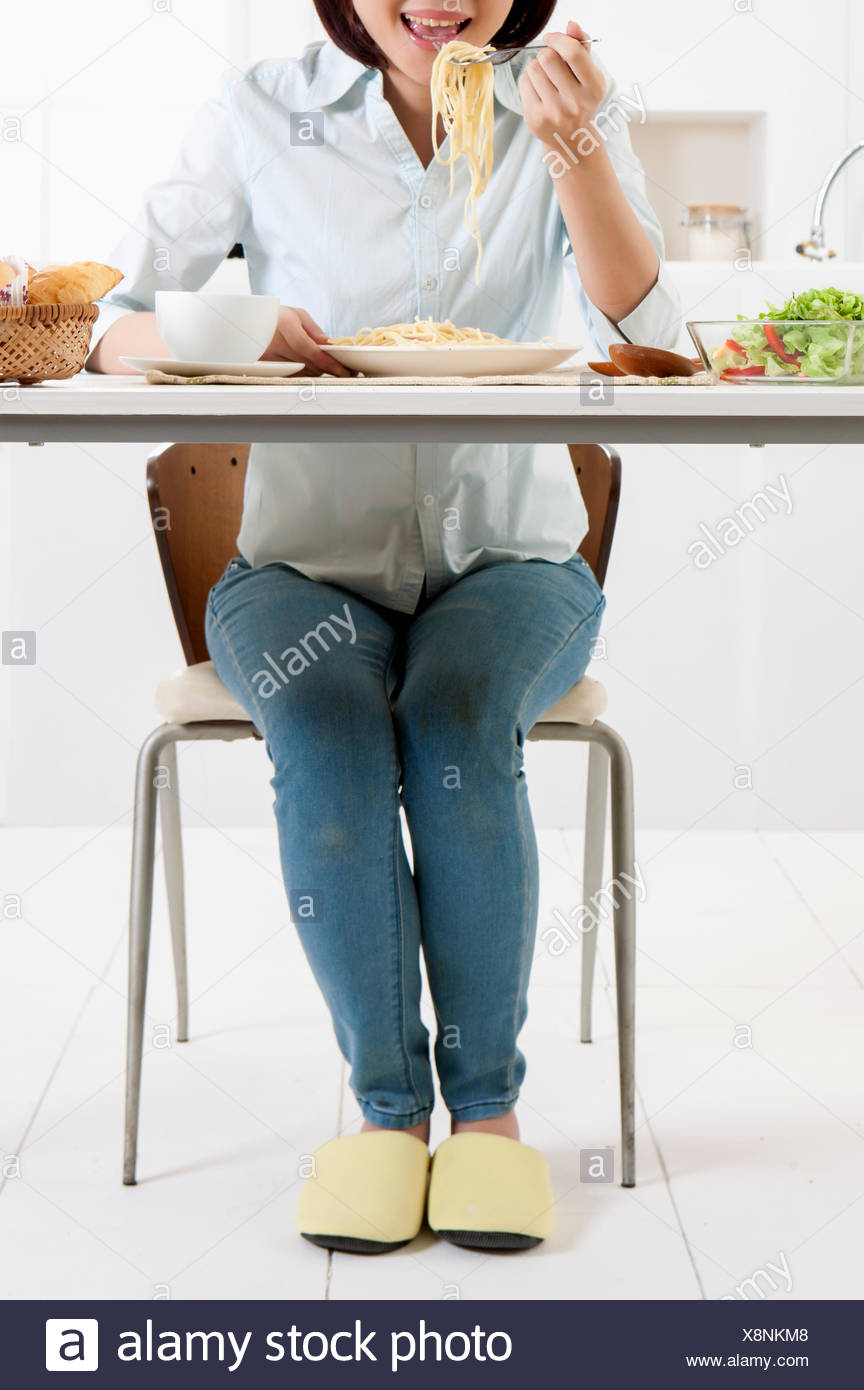 Young woman eating noodles with smile, - Stock Image