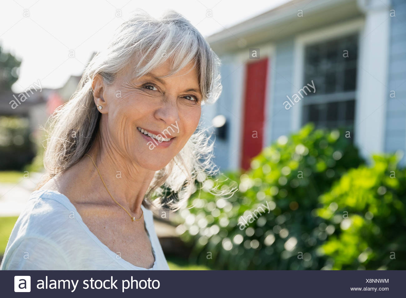 Portrait smiling senior woman in sunny front yard - Stock Image