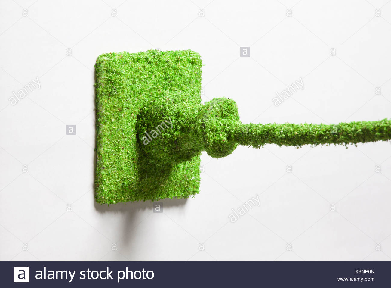 Power outlet covered with grass against white background - Stock Image