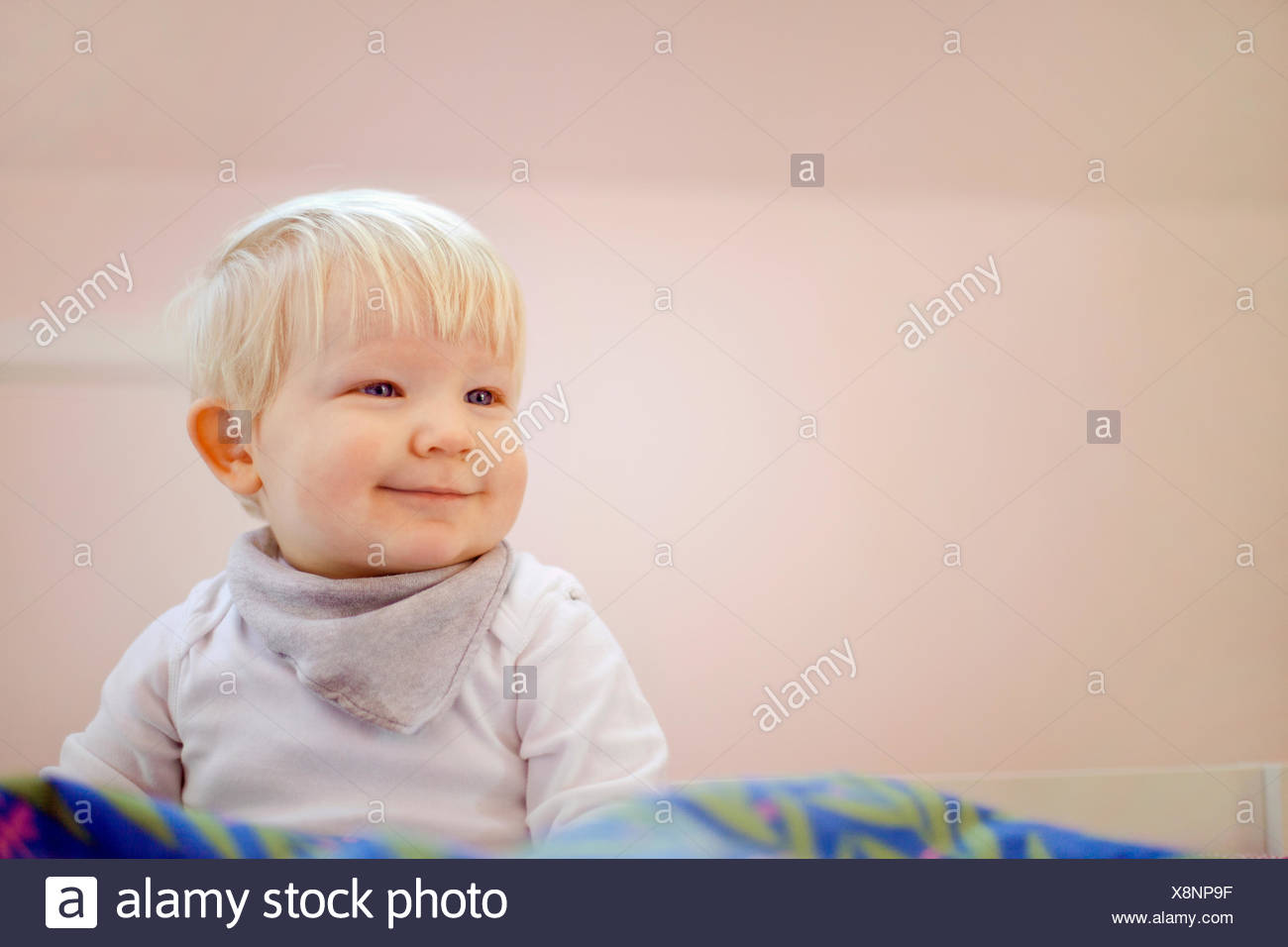 Portrait of cute fourteen month old baby boy sitting on duvet - Stock Image