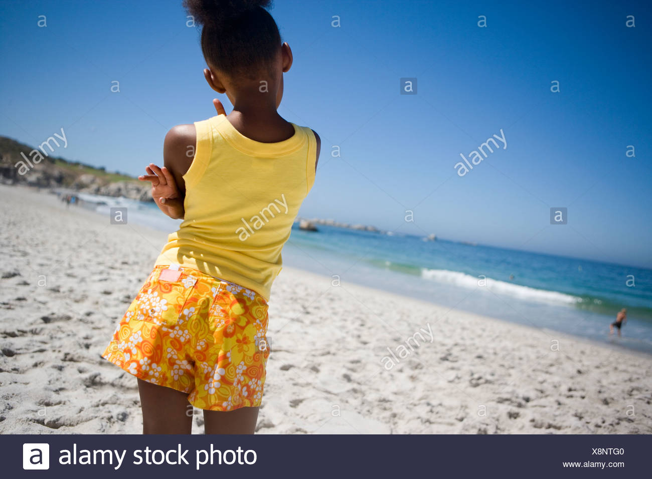Girl 9 11 in yellow vest and shorts standing on beach looking at sea rear view tilt - Stock Image