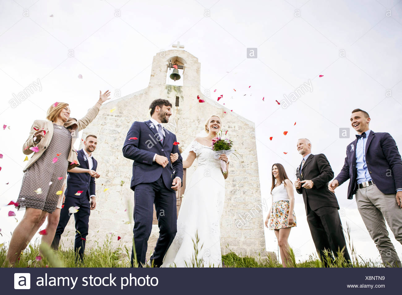 Guests throwing rose petals on bride and groom - Stock Image