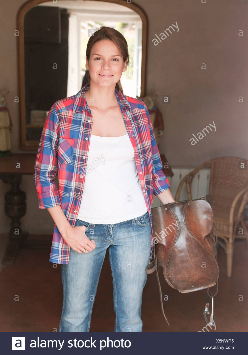 woman in doorway,smiling with saddle - Stock Image