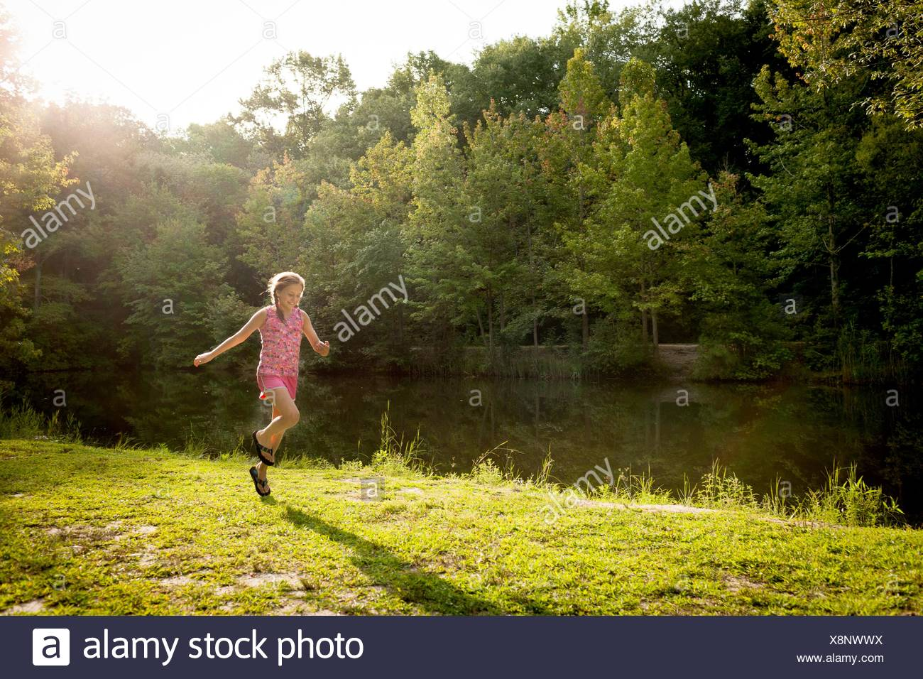 Girl skipping along river bank arms open - Stock Image