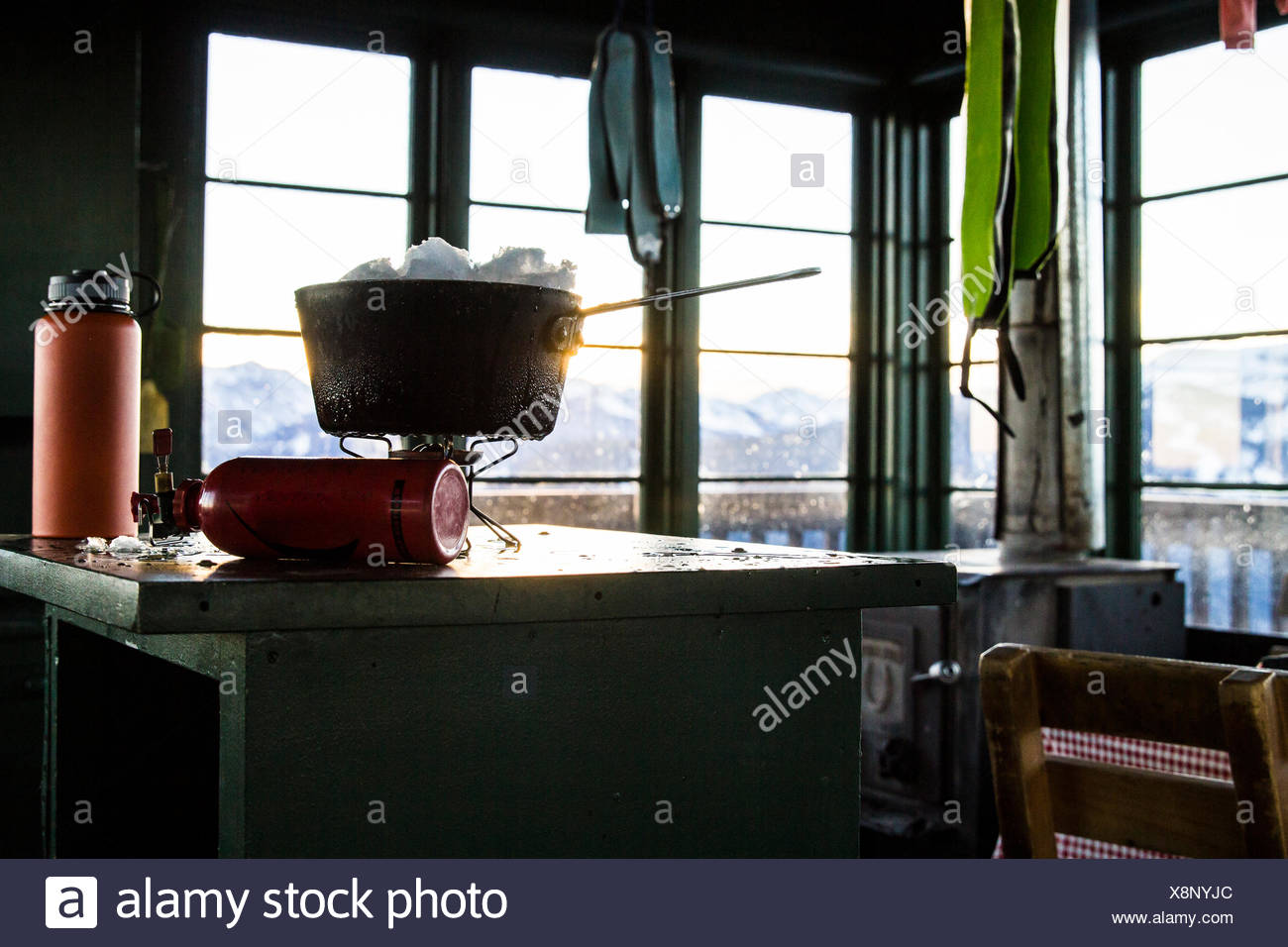 Melting snow for water on a camp stove in an old fire lookout in Montana. - Stock Image