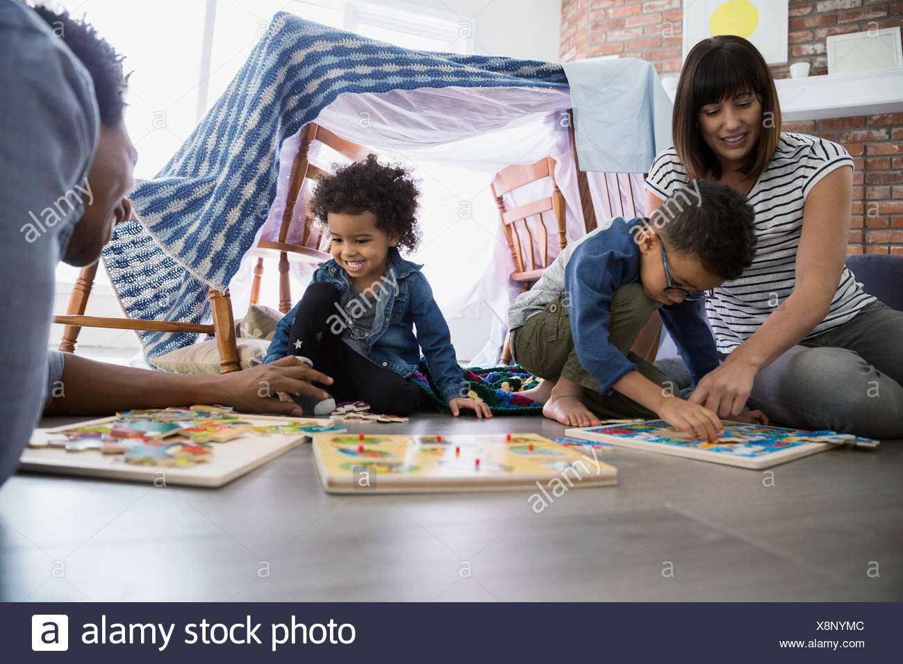 Family playing with jigsaw puzzles on floor - Stock Image