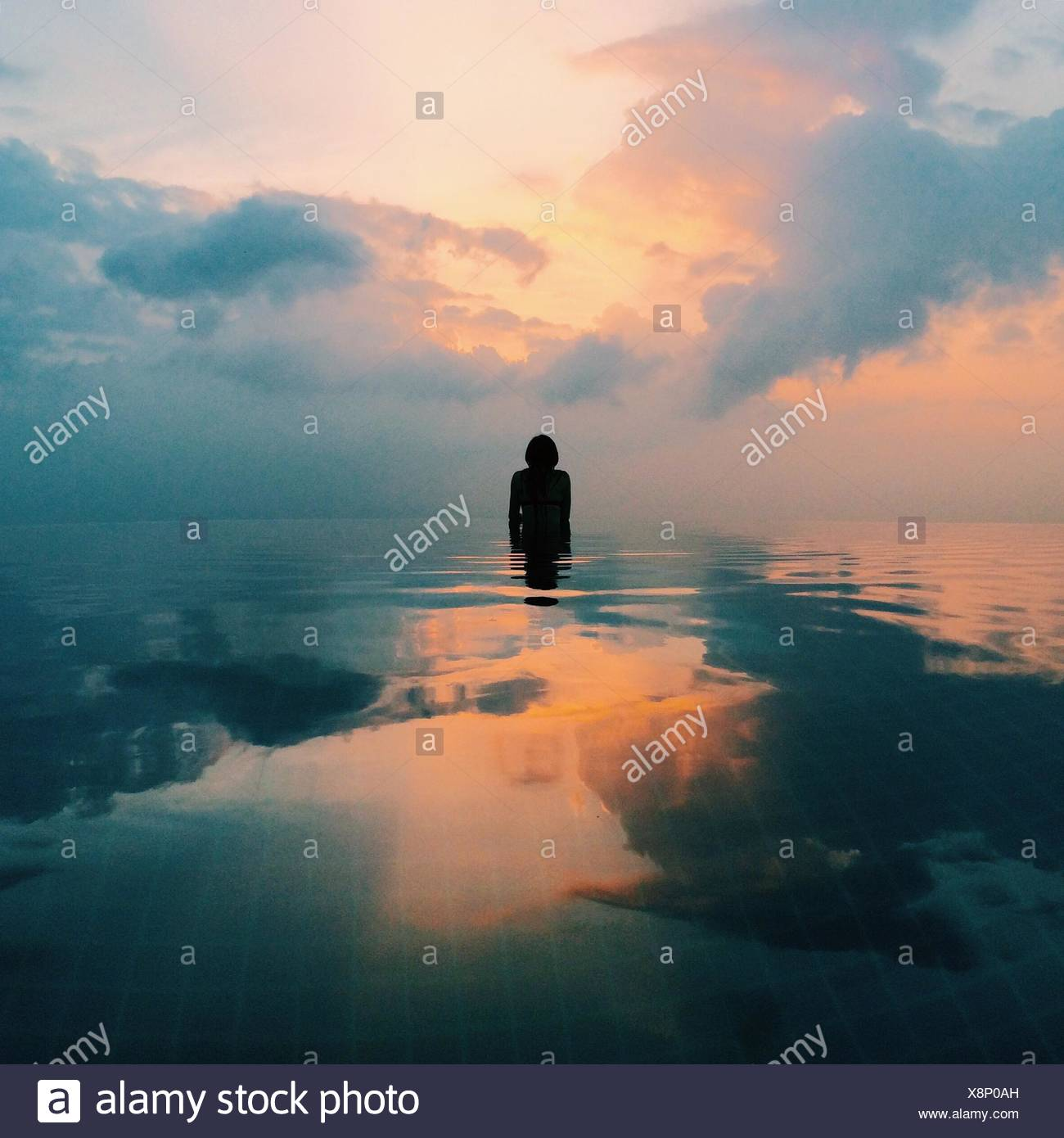 Person In Sea At Sunrise Stock Photo