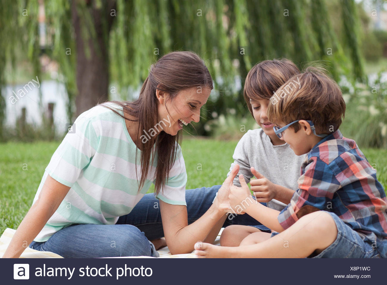 Mother teaching her sons how to thumb wrestle - Stock Image