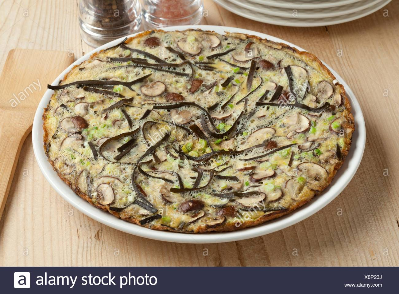 Omelet with sea spaghetti, mushrooms and spring onions. - Stock Image
