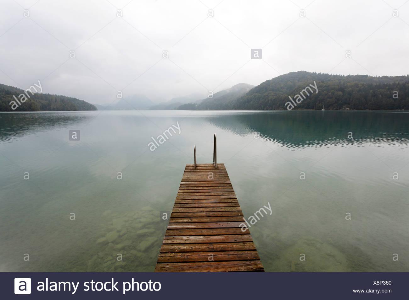 Wooden jetty juts into the Fuschlsee lake, overcast sky, rainy, dreary atmosphere, Salzkammergut area, Salzburger Land region,  - Stock Image