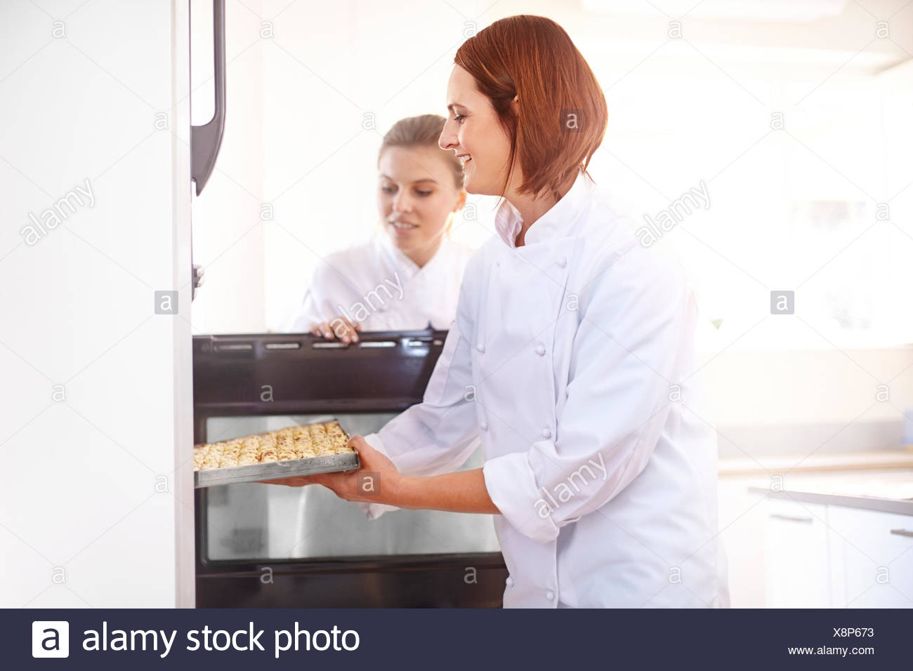 Chefs placing tray in oven - Stock Image
