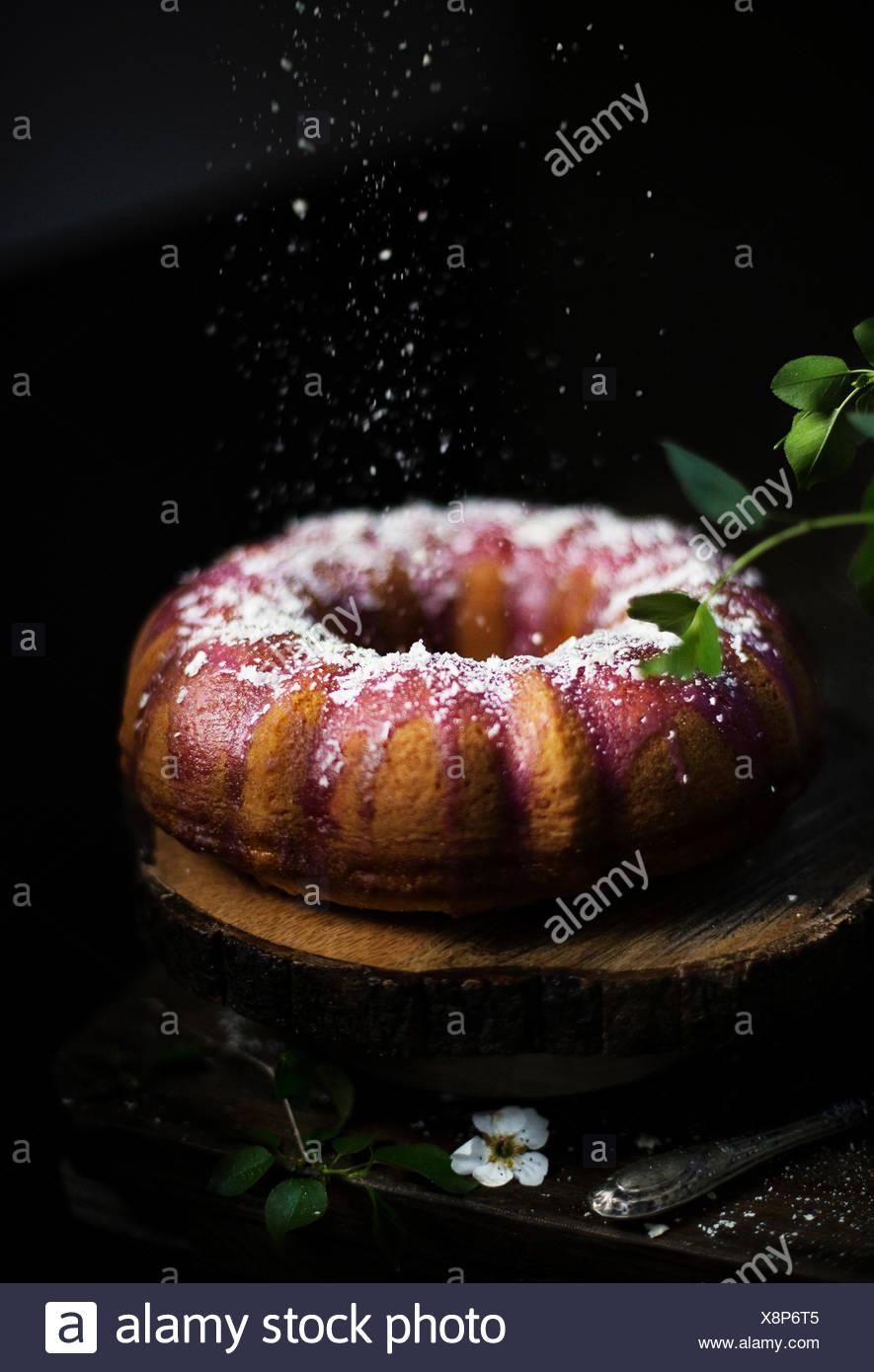 Bundt cake with blackberry glaze and white chocolate flakes - Stock Image
