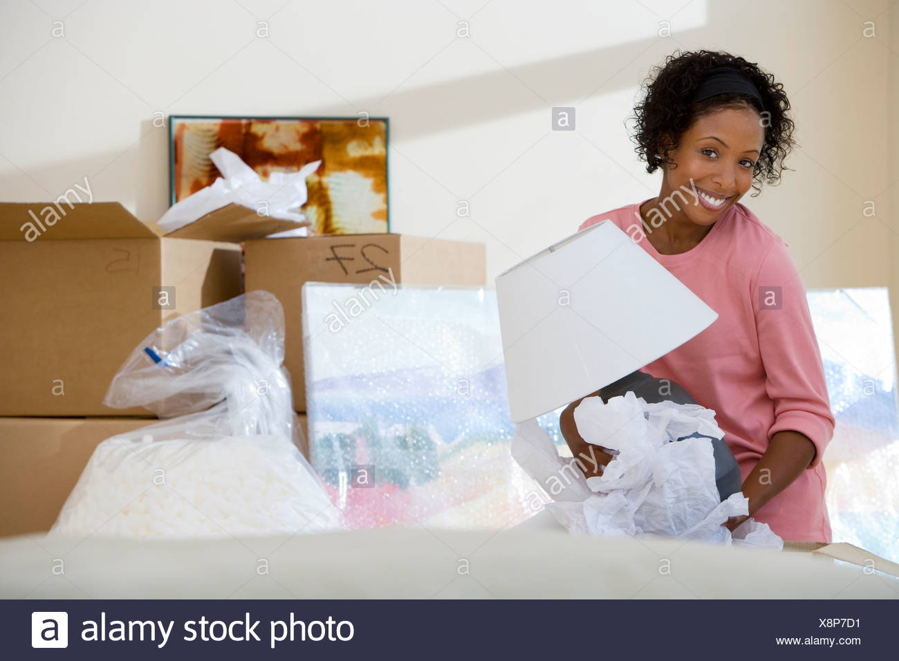 Woman moving house unpacking lamp from cardboard box in living room smiling portrait - Stock Image