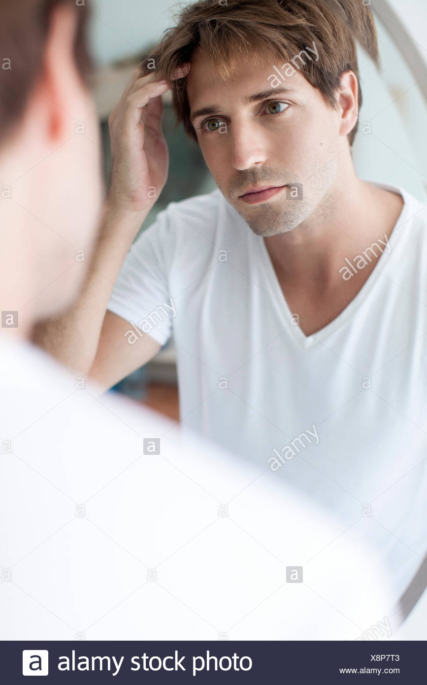 Man with receding hairline looking at self in mirror - Stock Image
